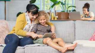 Woman and girl with tablet on couch