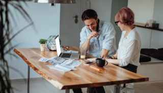 Two small business owners looking at their finances on a wooden table