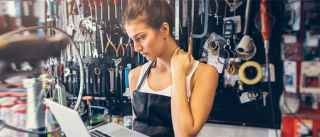 female bike repair shop owner look seriously at laptop