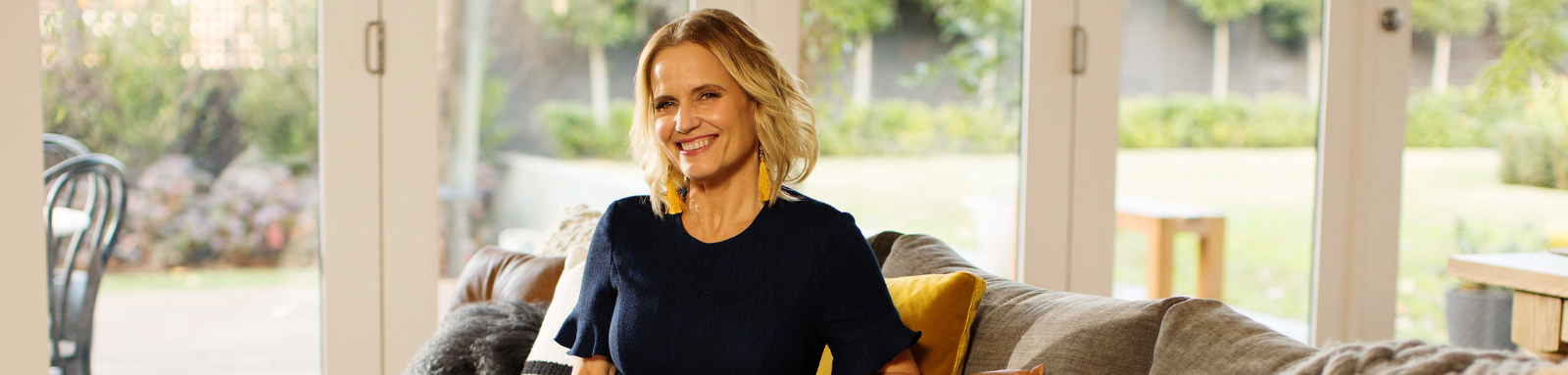 Shaynna Blaze sitting on couch