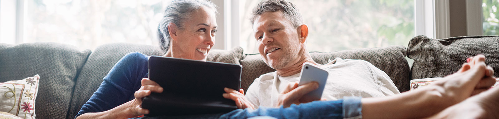 Two people sitting on couch using mobile phones