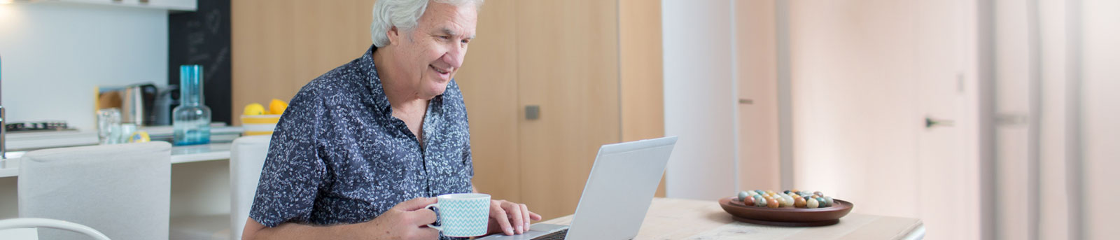 Older man looking at laptop in kitchen and holding mug