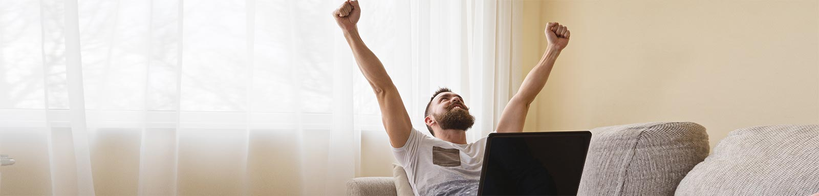 Happy freelancer celebrating on couch