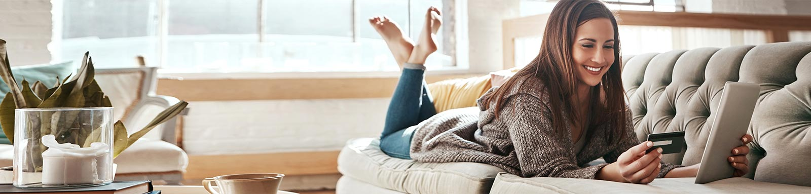 Woman holding ipad on a sofa at home
