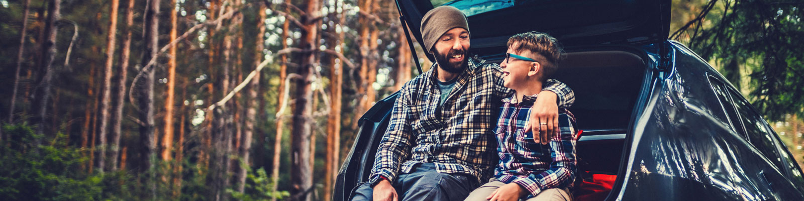 Father and son camping sitting in boot