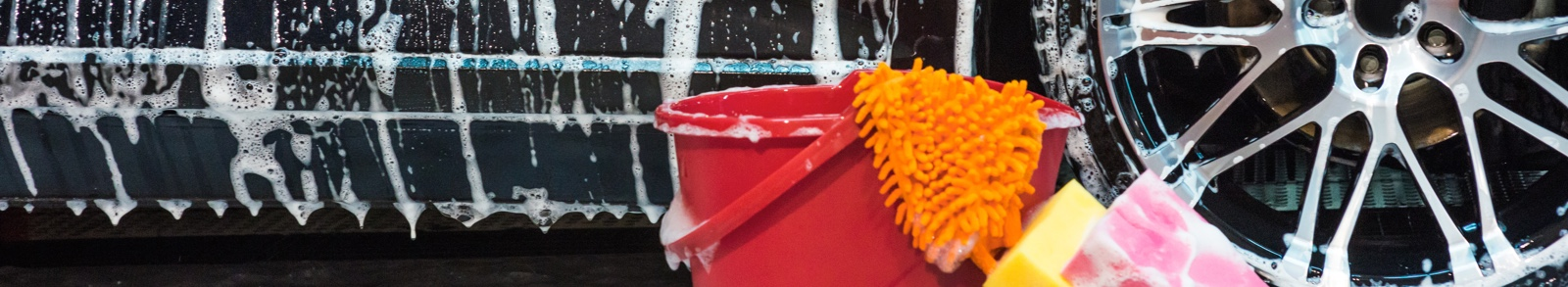 Car with soap suds and a red bucket with washing equipment