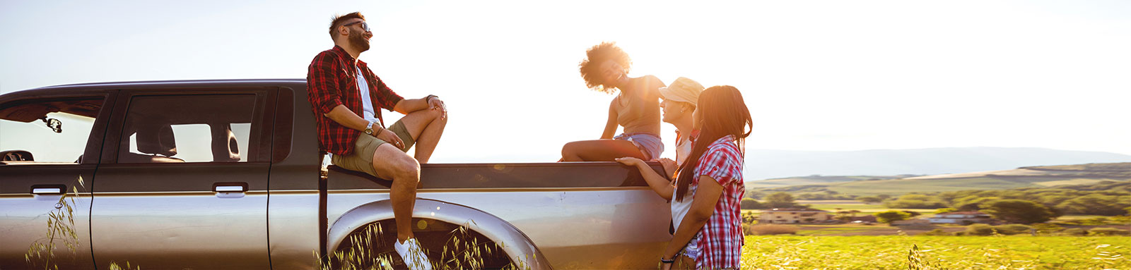A group of young adults stand around a ute in a field