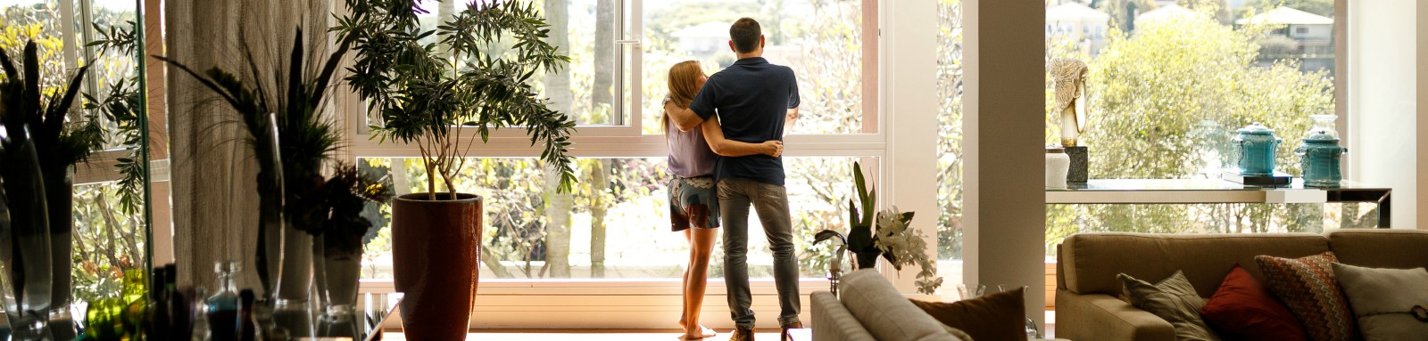 Couple looking outside living room window