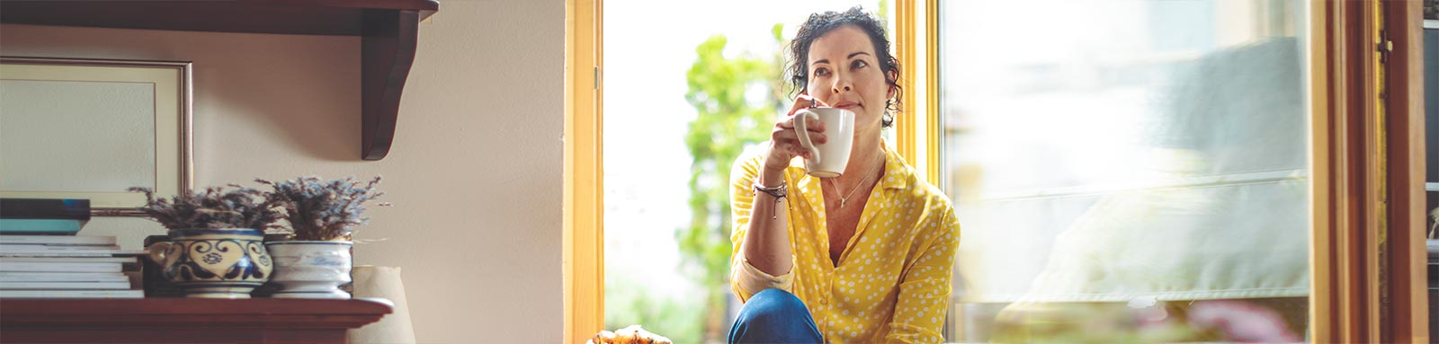 Woman thinking while drinking coffee by the window