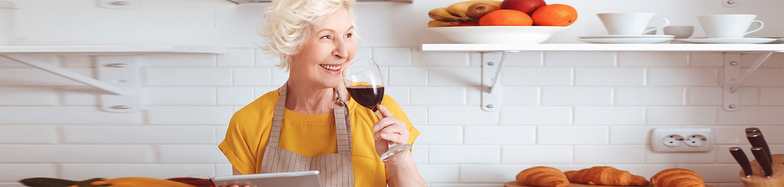 Elderly woman drinking red wine in the kitchen while holding tablet
