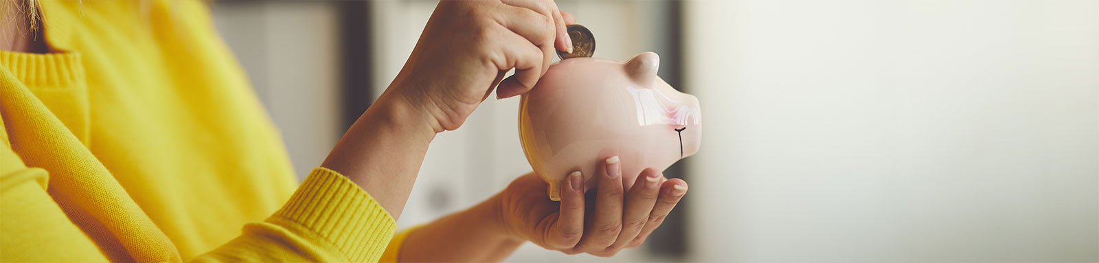 Woman putting coin in a pink piggy bank