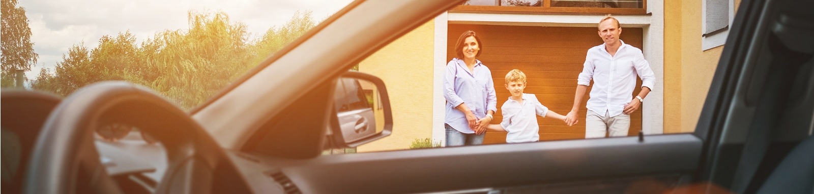 man woman and boy standing in front of a garage door next to a parked car