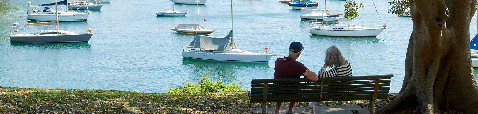 Elder couple sitting on bench gazing at river full  of boats