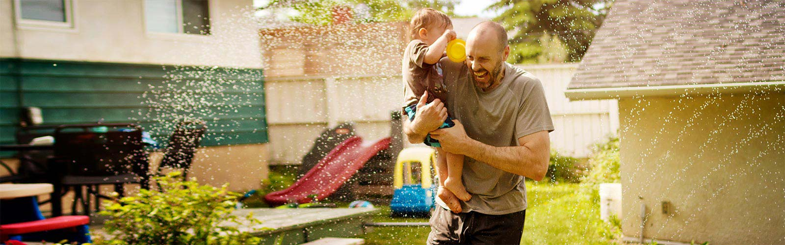 Father carrying son through water sprinkler backyard building