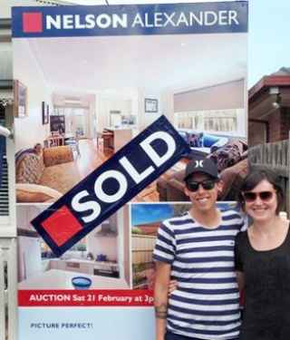 Couple standing in front of a sold sign